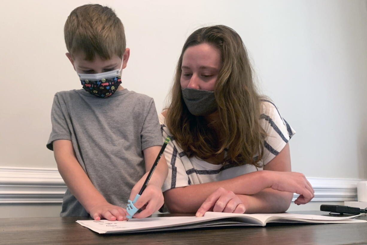 Emily Goss goes over school work at the kitchen table with her five-year-old son inside their Monroe, N.C., home on Monday, Sept. 13, 2021. The Goss' have decided to homeschool Berkeley after the Union County school district chose not to implement a mask mandate for children.