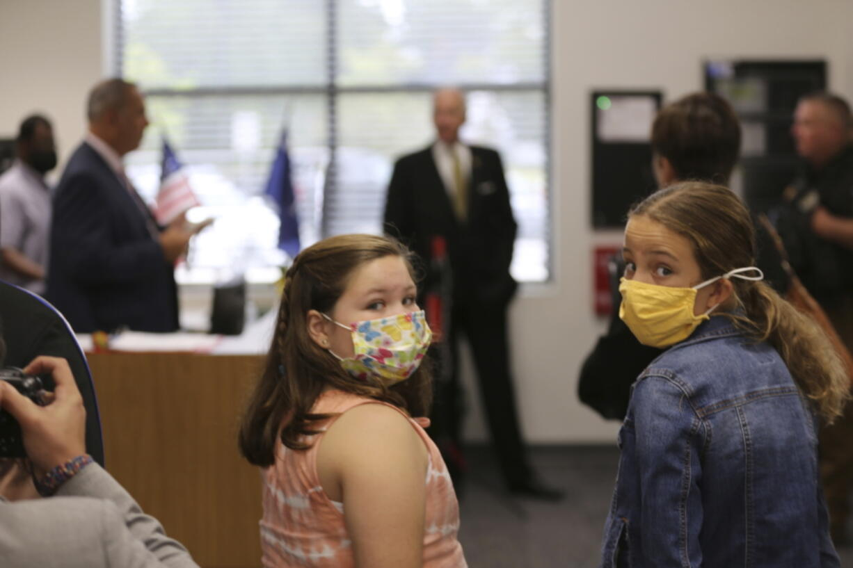 Two Camden Elementary School students in masks listen as South Carolina Gov. Henry McMaster talks about steps the school is taking to fight COVID-19, Wednesday, Sept. 15, 2021, in Camden, S.C. McMaster has adamantly and repeatedly come out against requiring masks in schools even as the average number of daily COVID-19 cases in the state has risen since early June.