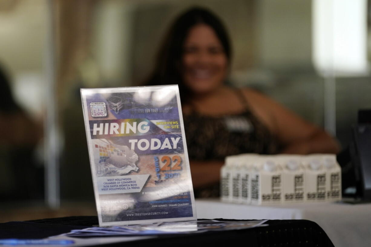 A hiring sign is placed at a booth for prospective employers during a job fair in September.(AP Photo/Marcio Jose Sanchez)
