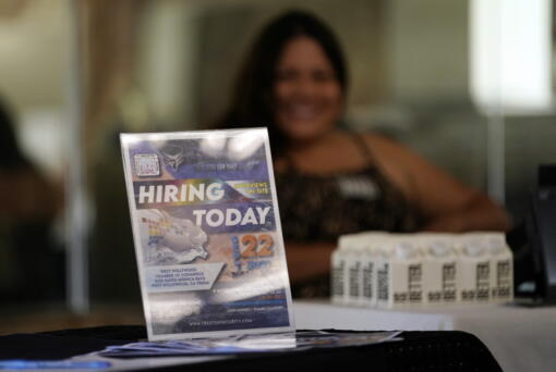 A hiring sign is placed at a booth for prospective employers during a job fair Wednesday, Sept. 22, 2021, in the West Hollywood section of Los Angeles.