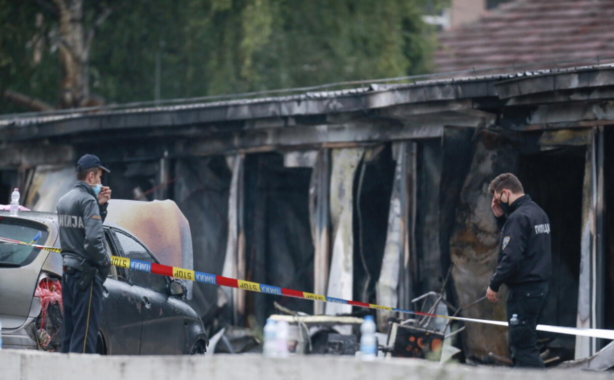 Police officers and forensics investigate the site at a burned out makeshift hospital after a fire in North Macedonia's northwestern city of Tetovo, early Thursday, Sept. 9, 2021. The blaze occurred late Wednesday at the makeshift hospital for COVID-19 patients.