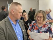 Brian Stransky, of unincorporated Sarpy County, Nebraska, listens as Citizens for Voter ID campaign official Nancy McCabe reads to him from a voter ID ballot petition on Thursday, Sept. 2, 2021, at a local Republican Party meeting in Papillion, Nebraska. Activists who want to require voters to show a government-issued identification at the polls are taking the issue directly to voters after facing years of rejection in the Nebraska Legislature.