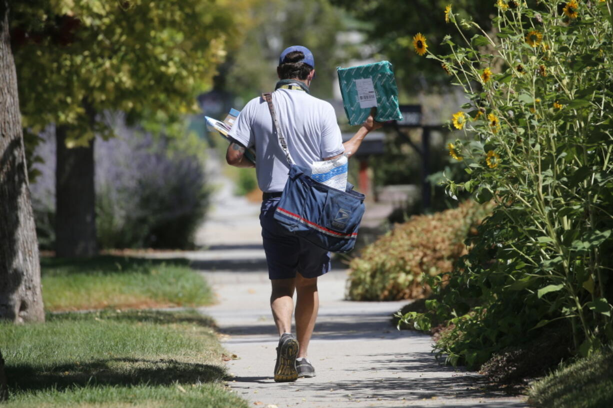 FILE - In this Aug. 17, 2020, file photo, a United States Postal Service carrier delivers mail to homes in Salt Lake City. A Center for Public Integrity investigation finds that the U.S. Postal Service regularly cheats mail carriers out of their pay. Arbitrators and federal investigators have found managers at hundreds of post offices around the country have illegally underpaid hourly workers for years.