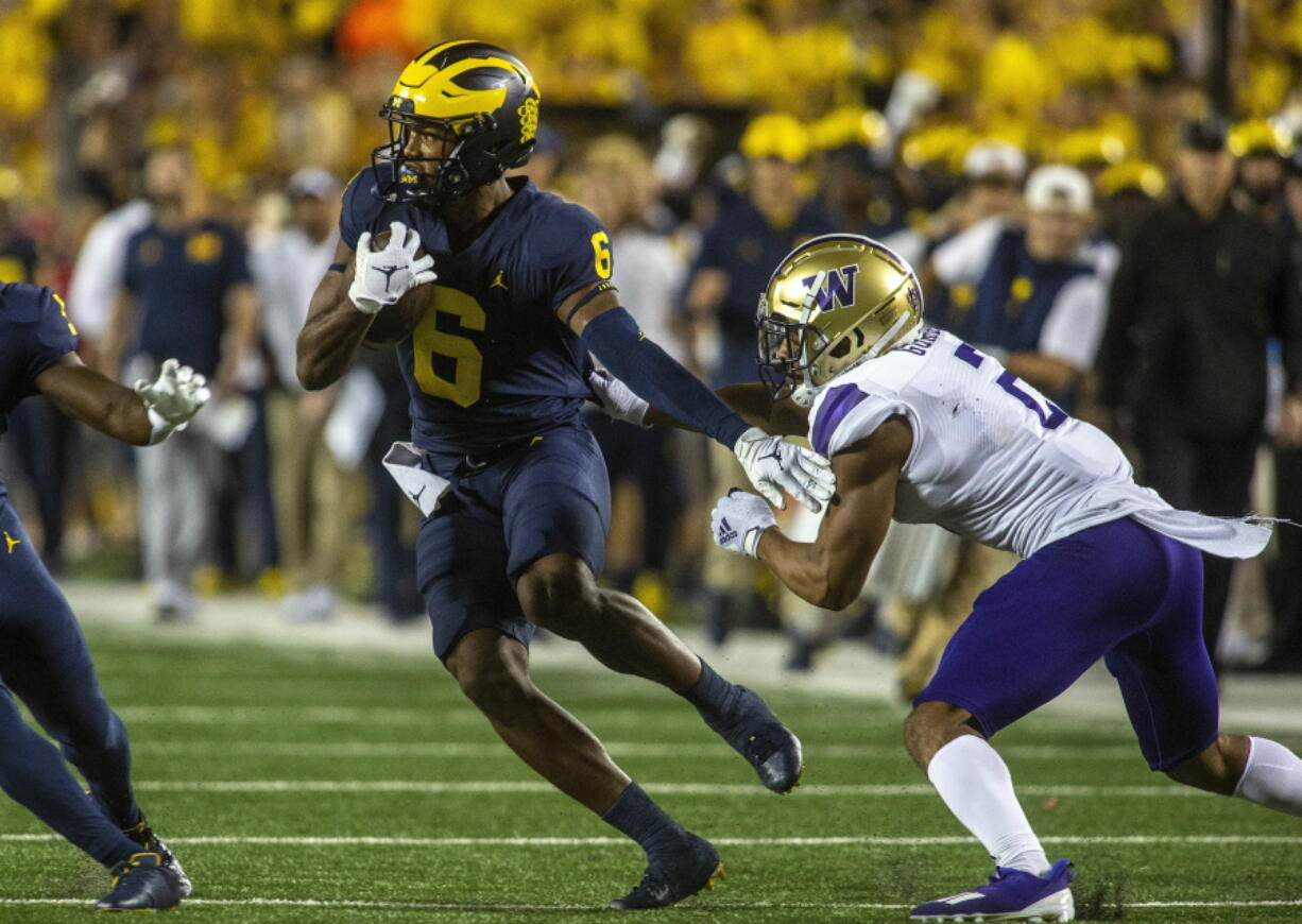 Michigan wide receiver Cornelius Johnson (6) rushes away from Washington defensive back Kyler Gordon, right, in the first quarter of an NCAA college football game in Ann Arbor, Mich., Saturday, Sept. 11, 2021.
