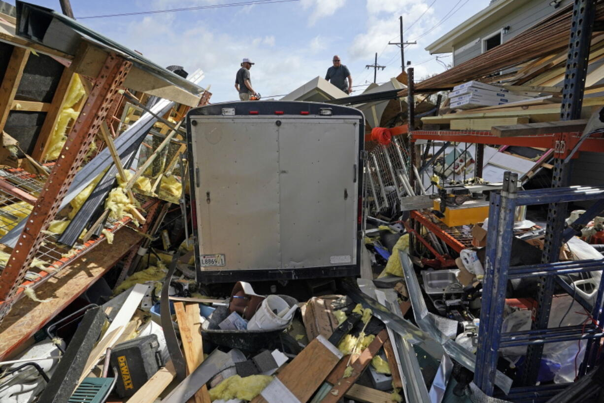 FILE - In this Monday, Aug. 30, 2021, file photo, Jacob Hodges, right, and his brother Jeremy Hodges work to clear debris from their storage unit which was destroyed by Hurricane Ida, in Houma, La. A new report from the United Nations weather agency finds the world is getting several times more weather disasters than in the 1970s. (AP Photo/David J.