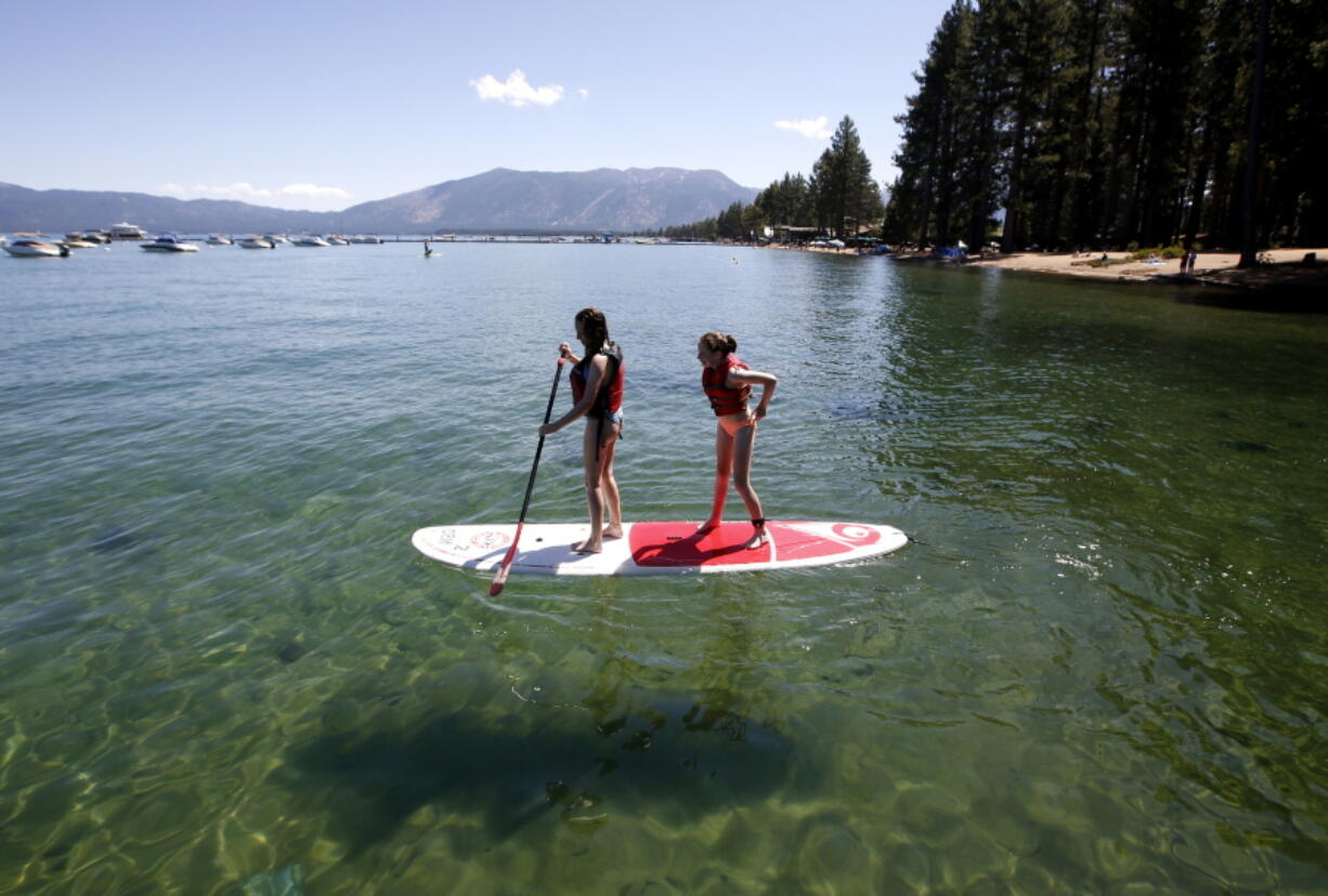 FILE - In this Aug. 20, 2019, file photo, Freya Mayo, left, and her sister Evie, of London, try out a paddle board on Lake Tahoe near South Lake Tahoe, Calif. With wildfire no longer threatening Lake Tahoe, residents, tourists and scientists drawn to its clean alpine air, clear blue waters and fragrant pine trees now wonder about the long-term effects that will remain after wildfire season ends.
