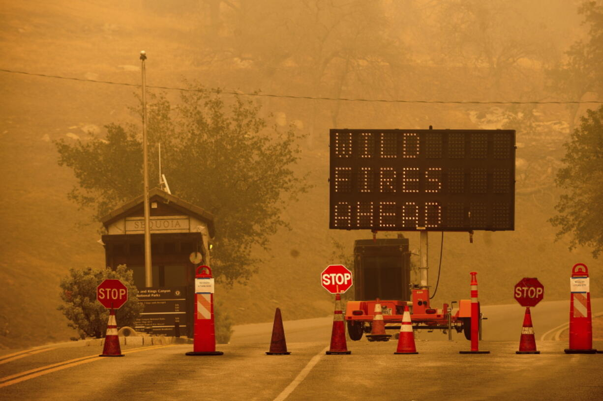 Cones block the entrance to Sequoia National Park, Calif., as the KNP Complex Fire burns nearby on Wednesday, Sept. 15, 2021. The blaze is burning near the Giant Forest, home to more than 2,000 giant sequoias.