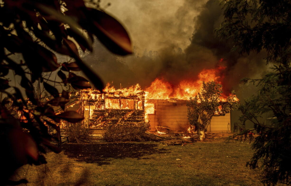 Flames consume a house near Old Oregon Trail as the Fawn Fire burns north of Redding in Shasta County, Calif., on Thursday, Sept. 23, 2021.
