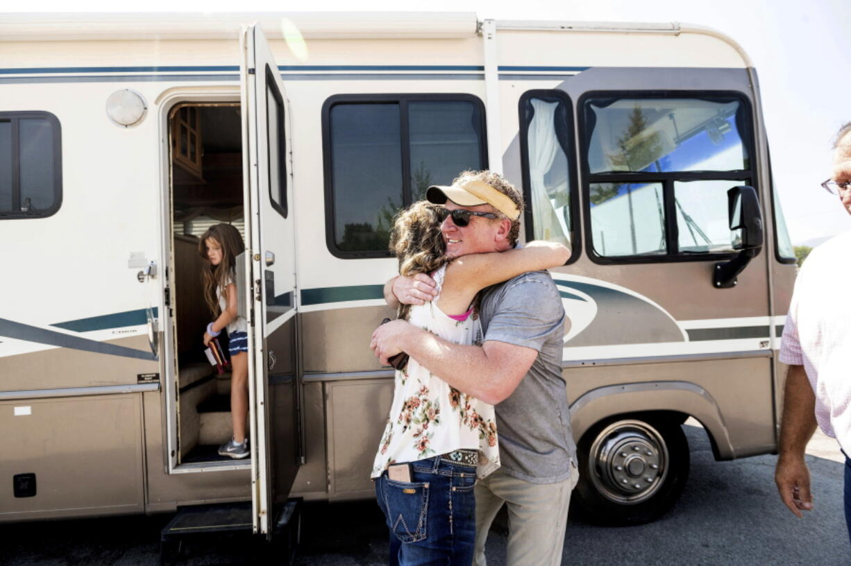 Woody Faircloth hugs Sheri Roen as her family donates their motorhome to EmergencyRV.org on Sept. 5 in Sierra County, Calif. Accompanied by daughter Luna, left, Faircloth delivered it to a Dixie Fire victim later that day.