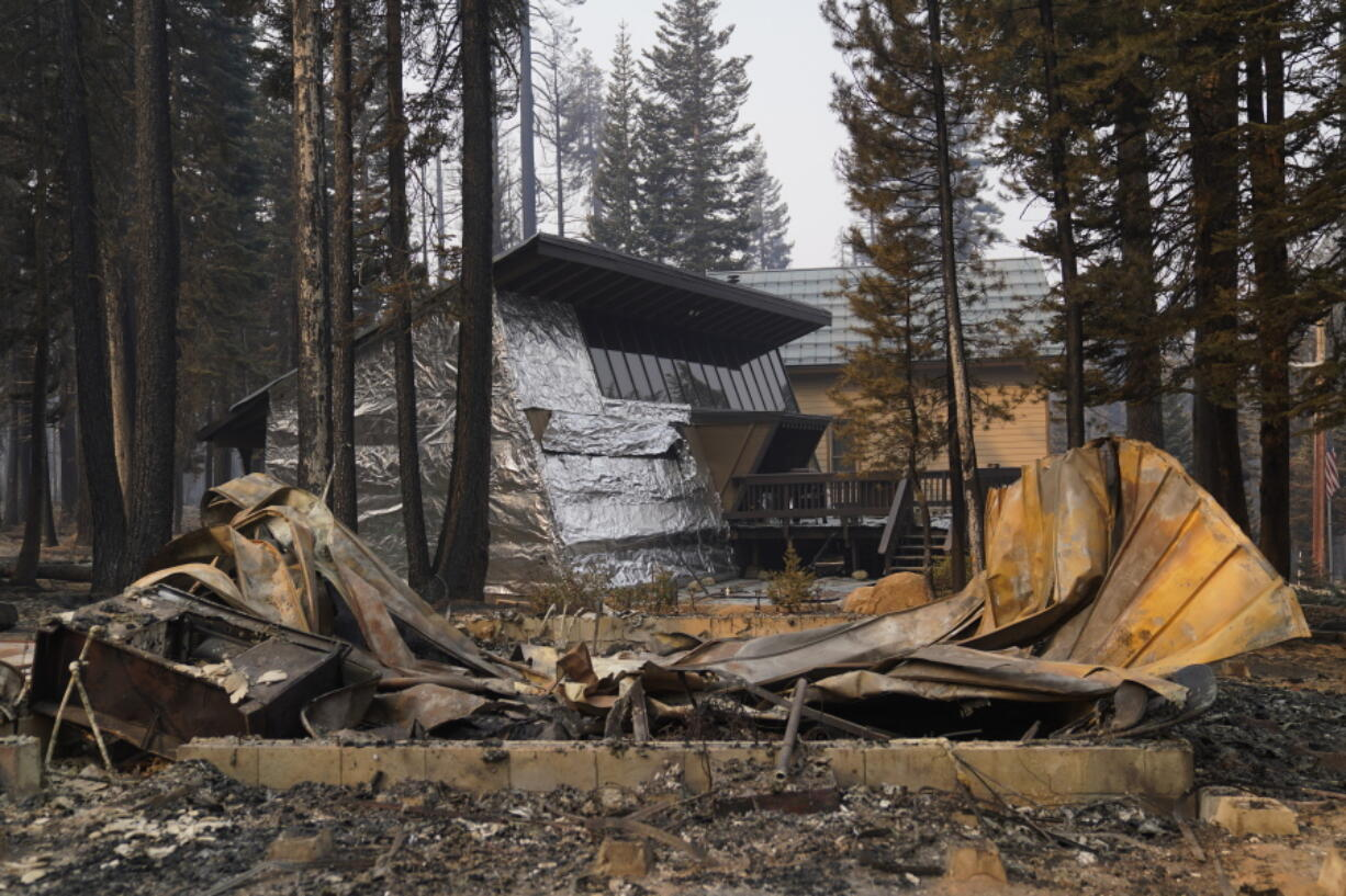 FILE - In this Sept. 2, 2021 file photo a cabin partially covered in fire-resistant material stands behind a property destroyed in the Caldor Fire in Twin Bridges, Calif.  Aluminum wraps designed to protect homes from flames are getting attention as wildfires burn in California. During a fire near Lake Tahoe, some wrapped houses survived while nearby homes were destroyed. The material resembles tin foil from the kitchen drawer but is modeled after the tent-like shelters that wildland firefighters use as a last resort to protect themselves when trapped by flames.  (AP Photo/Jae C.