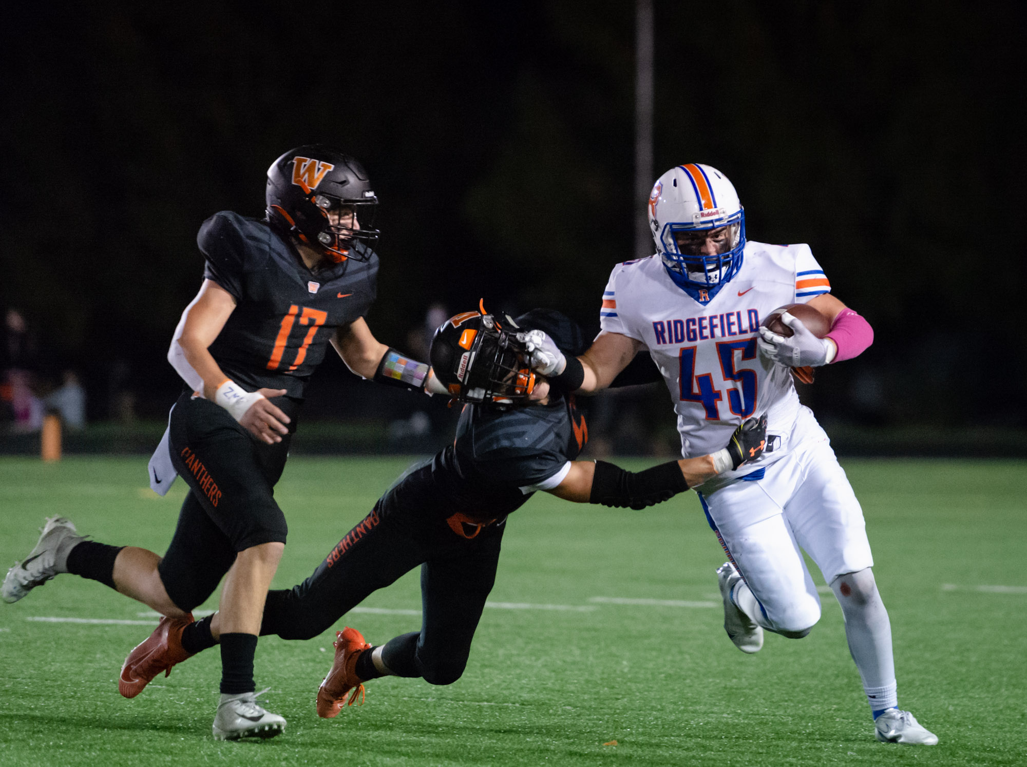 Ridgefield's Connor Delamarter stiff arms a Washougal defender in a 2A Greater St. Helens League football game on Friday, Oct. 1, 2021, at Fishback Stadium in Washougal.