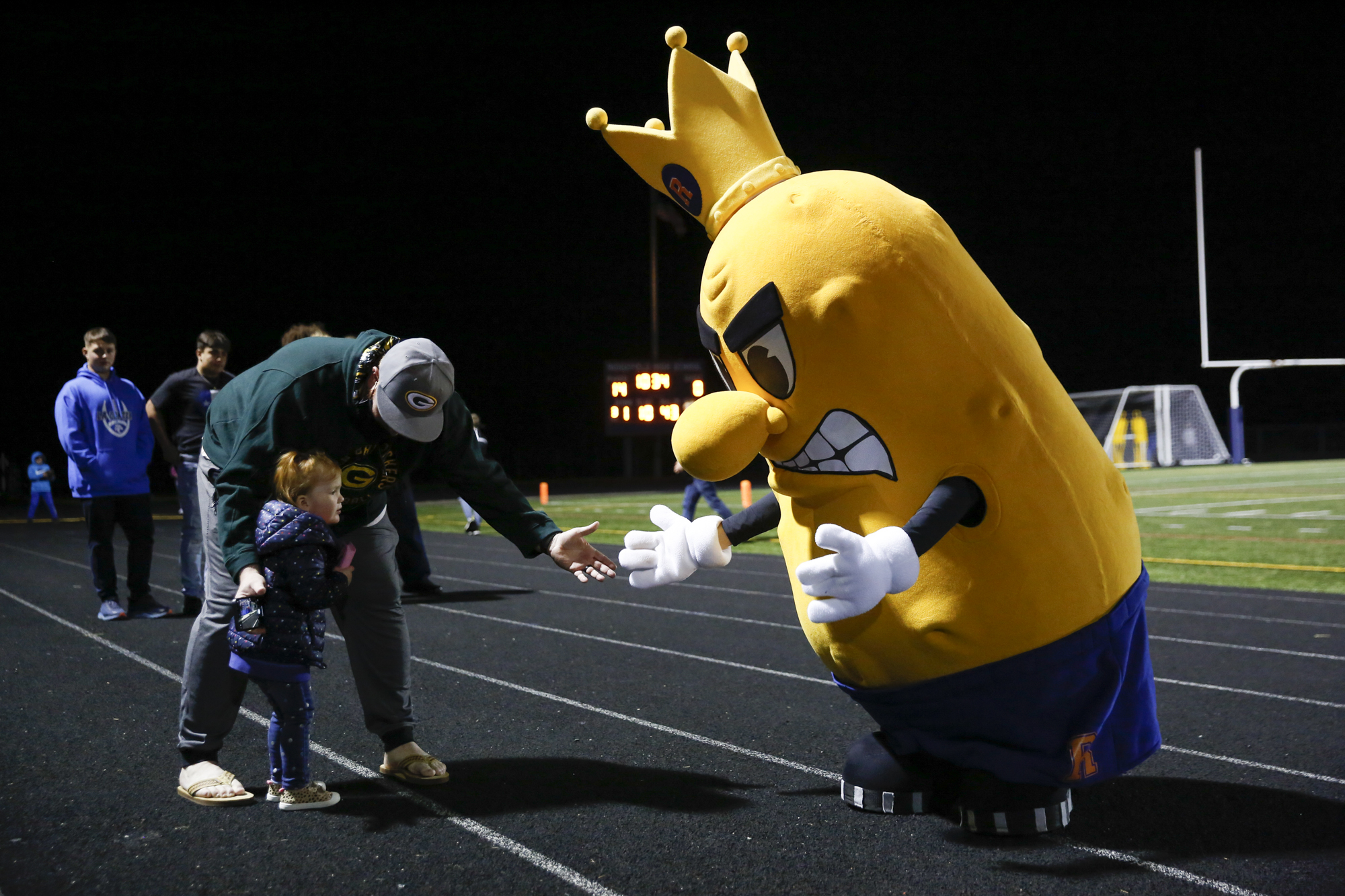 A young fan meets the Ridgefield Spudders team mascot during a 2A Greater St. Helens League football game at Ridgefield High School on Thursday, Oct. 7, 2021.