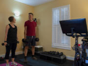 Amy Hawkins and Ben Novinger begin a workout at their home in Portland. They are participants in a OHSU's Knight Cancer Institute trial program called Exercising Together. Continuing research demonstrates that exercise is beneficial during and after cancer treatment.