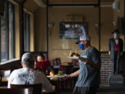 Bartender Mike Dunning serves lunch in the dining room at Main Event East.