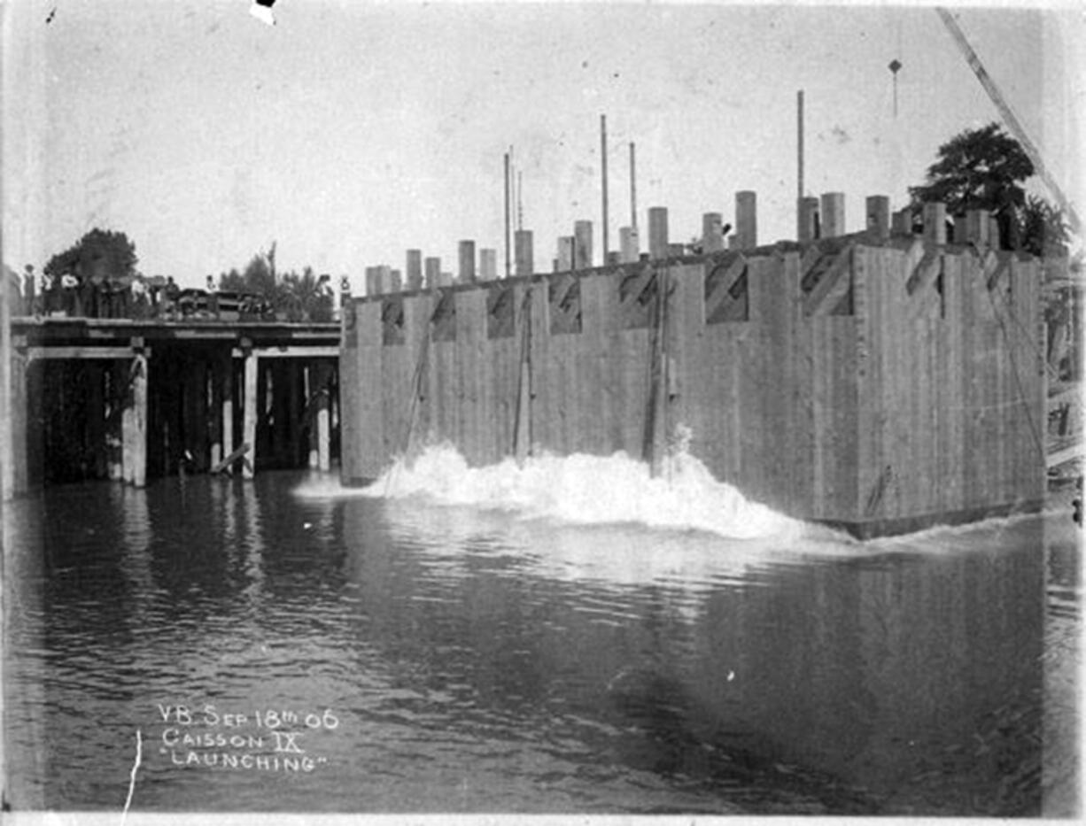 This concrete box allowed workers access to the floor of the Columbia River to anchor and build the bridge piers holding up the Portland-Vancouver railway bridge connecting Oregon and Washington. This 1906 photo shows the caisson (box) being lowered into the river. About two years later, regularly scheduled trains crossed the two-rail bridge daily in both directions, north and southbound.