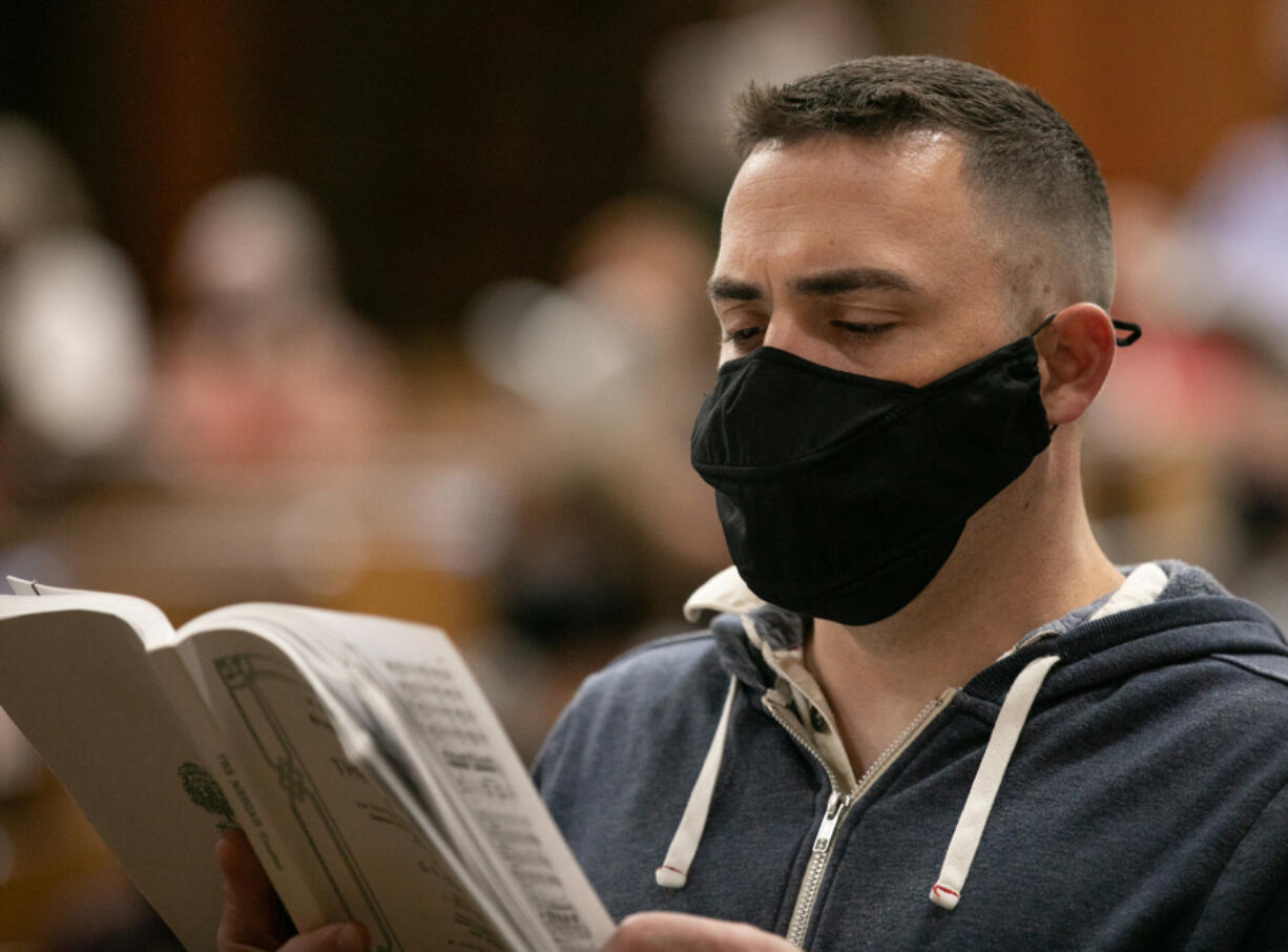 """Roberto Rodriguez/ for The Columbian Vancouver Master Chorale member Ryan Allen of Vancouver sings while wearing a face mask designed for singing during rehearsal at First Presbyterian Church. """"It feels very different,"""" Allen said. """"I can breathe, and I can actually hear my voice going out."""" (Roberto Rodriguez for The Columbian)"""