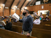 """Ryan Allen, a longtime member of the Vancouver Master Chorale, focuses on the music Monday while wearing a face mask specifically designed for singing during a recent rehearsal at First Presbyterian Church. """"It feels very different,"""" Allen said."""