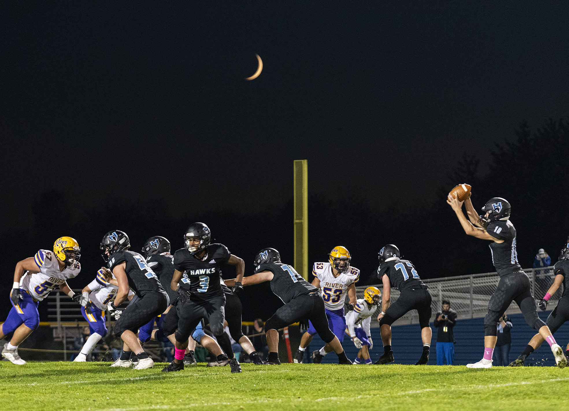 A waxing crescent moon hangs above the Hockinson High School football field Friday, Oct. 8, 2021, during the Hawks' 31-6 win against Columbia River.