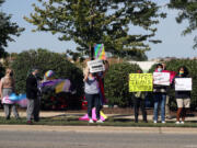 Protesters hold signs Sept. 24 across from St. Francis High School in Wheaton, Ill., calling for recognition of nontraditional personal pronouns used by queer and transgender students.