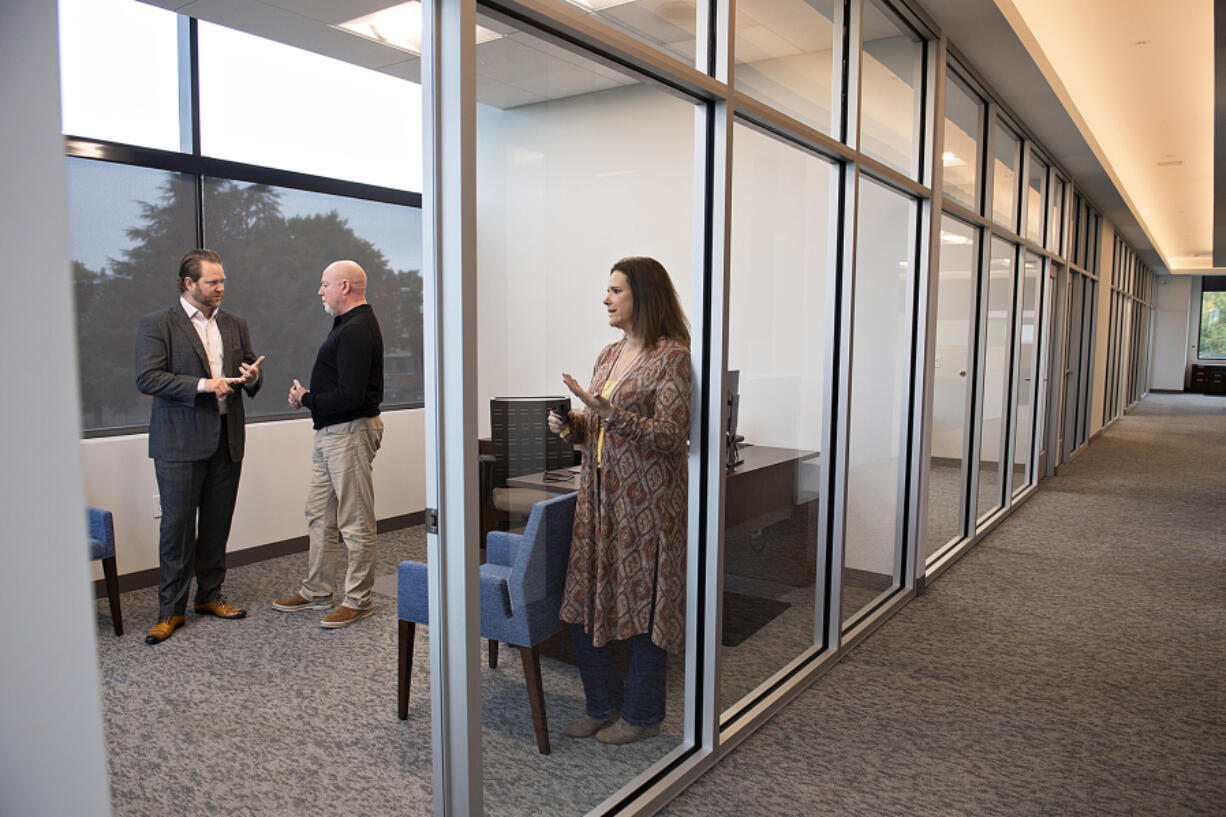 Al Angelo Co. President Albert Angelo III, left, chats with Scott Wilcox and Bari Smith of JD Fulwiler & Co. Insurance in the commercial side of Vancouver's newest building, the Angelo Tower.