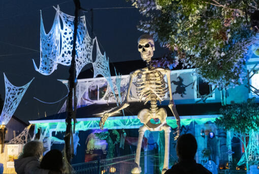 A 12-foot tall skeleton looms over people looking at Halloween decorations the Mains' house on Franklin Street in Vancouver earlier this month.