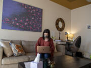 """Kendall Hagensen of The Vancouver Wellness Studio is pictured in her office while looking over her laptop. """"We're seeing collective trauma,"""" she said about workers in the pandemic."""