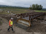 Chris Collins, project manager for the Lower Columbia Estuary Partnership, walks past a new trail bridge crossing the levee breach to the Columbia River at the Steigerwald Lake National Wildlife Refuge on Wednesday morning.