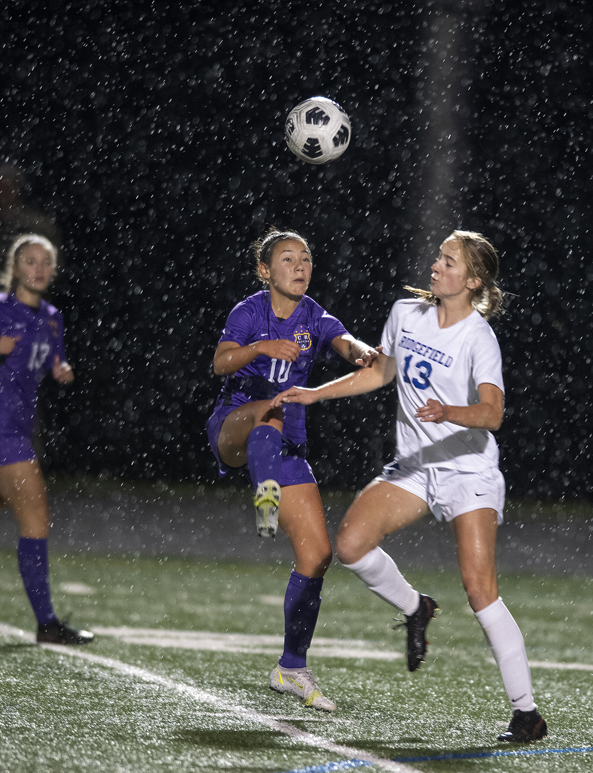 Columbia River's Andie Buckley (10) and Ridgefield's Cameron Jones (13) handle a header in the first half at Columbia River High School on Tuesday night, Oct. 12, 2021.