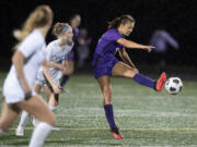 Ridgefield's Eliana Petersen (5) defends as Columbia River's Anna Iniguez (12) connects with the ball in the first half at Columbia River High School on Tuesday night, Oct. 12, 2021.