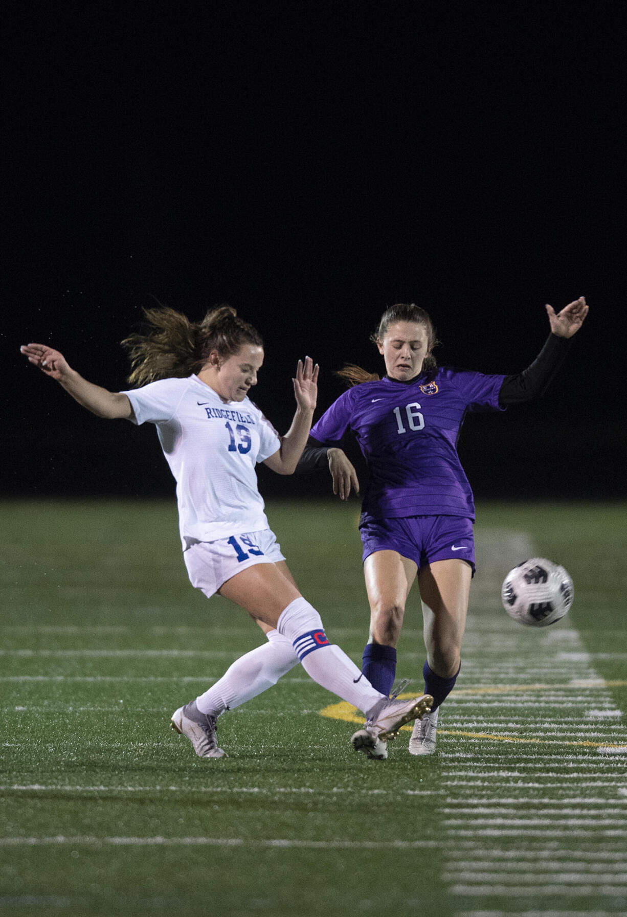 Ridgefield's Paytn Barnette (19) and Columbia River's Kinzi Drake (16) battle for the ball in the first half at Columbia River High School on Tuesday night, Oct. 12, 2021.