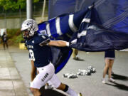 Skyview senior Jaydin Knapp bursts through a banner Thursday, Oct. 14, 2021, at the start of the game between Union and Skyview at the Kiggins Bowl in Vancouver.