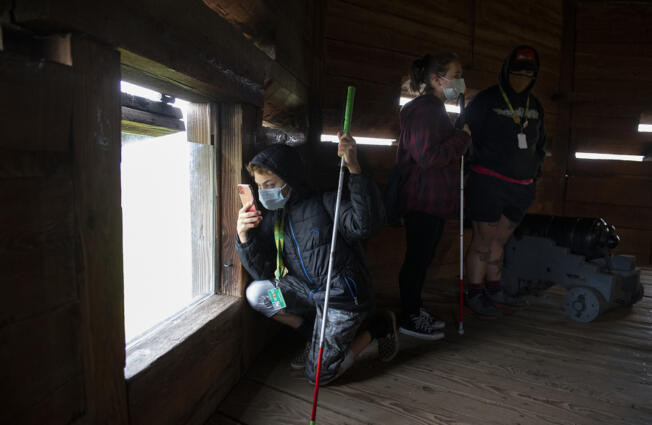 Above, seventh-grader Dezmynd Cantu, left, kneels to snap a photo while touring the bastion at Fort Vancouver National Historic Site with classmate Brianna Hoefliner and paraeducator Jared Miller-Price.