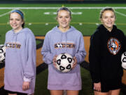 From left, Molly, Emily and Lauren Rabus pose for a portrait after a practice on Monday, Oct. 18, 2021, at Washougal High School.