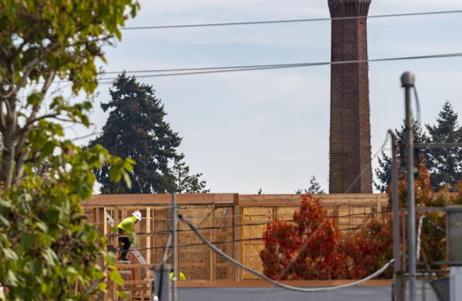 Construction workers continue building an apartment building Tuesday, Oct. 19, 2021, as the Providence Academy smokestack stands in the distance. The Vancouver City Council decided Monday to uphold a demolition permit for Providence Academy's landmark smokestack.