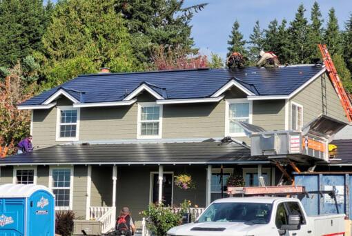 Crews install a new Tesla roof at Dave Miller's Camas home. At top: The glass photovoltaic tiles in a Tesla roof are stronger than standard roofing tiles, according to the company. (Photos contributed by Dave Miller)