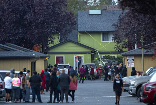 People gather at Alder Creek Apartments and Townhomes after a shooting in northeast Vancouver on Tuesday evening, Oct. 19, 2021. The apartment complex is just west of the location where Clark County sheriff's deputies fatally shot a suspect in an assault on Sunday.