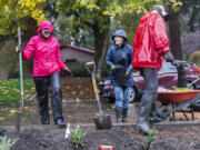 Suzanne Mickelson, left, and Ellen Zacny, center, laugh while planting foliage in the Riveridge Neighborhood cul-de-sac island on Saturday morning.
