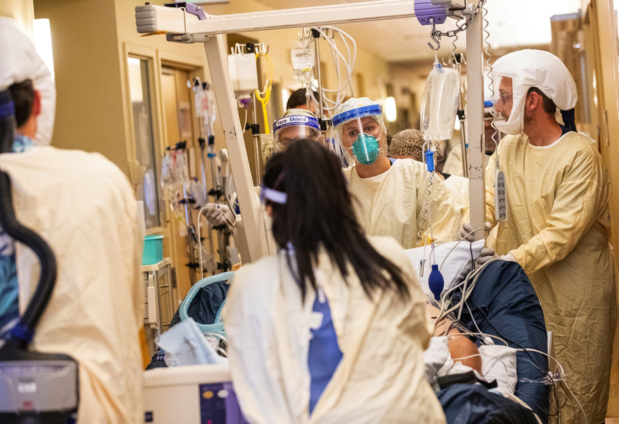 A medical team moves a COVID-19 patient to a new room in the ICU at Central Washington Hospital on Tuesday, Sept. 21, 2021.