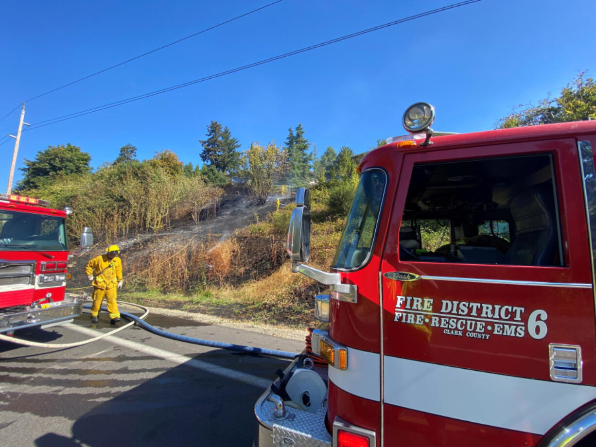 Firefighters from Fire District 6 extinguish a brush fire last month above Northwest Lakeshore Avenue. The district is one of four with contested races for commissioner seats in the Nov. 2 election.