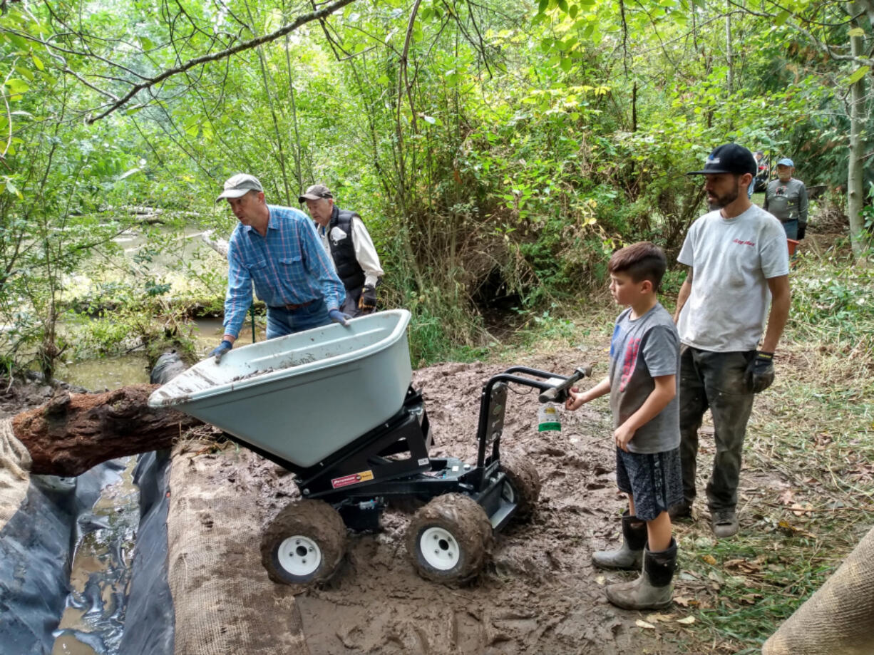Volunteers with Trout Unlimited dig the new inflow channel to bring cold spring water into a pond in the Salmon Creek watershed. The new channel corrected a flaw in the habitat project's original design.