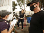 Zack Gustine, right, who is unhoused living near Lincoln Park, and Chelsea Shover, PhD, UCLA School of Medicine, left, encourage Kimberly Conti to get the COVID vaccine shot on Thursday, Oct. 7, 2021, in Los Angeles.