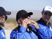 """William Shatner, center, describes what the g-forces of the Blue Origin lift off did to his face as Chris Boshuizen, left, and Glen de Vries all look on during a media availability at the spaceport near Van Horn, Texas, Wednesday, Oct. 13, 2021.  The """"Star Trek"""" actor and three fellow passengers hurtled to an altitude of 66.5 miles (107 kilometers) over the West Texas desert in the fully automated capsule, then safely parachuted back to Earth in a flight that lasted just over 10 minutes."""