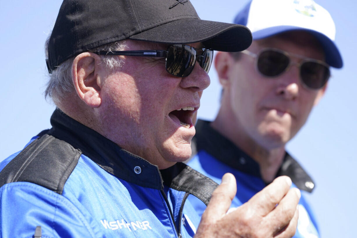 """William Shatner, center, describes his flight on the Blue Origin as Glen de Vries looks on during a media availability at the spaceport near Van Horn, Texas, Wednesday, Oct. 13, 2021.  The """"Star Trek"""" actor and three fellow passengers hurtled to an altitude of 66.5 miles (107 kilometers) over the West Texas desert in the fully automated capsule, then safely parachuted back to Earth in a flight that lasted just over 10 minutes."""