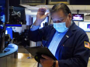 Trader John Santiago works on the floor of the New York Stock Exchange, Tuesday, Oct. 19, 2021. Stocks are moving modestly higher on Wall Street in early trading Tuesday as corporate earnings reporting gets into full swing.