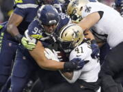 Seattle Seahawks defensive end Rasheem Green (94) brings down New Orleans Saints running back Alvin Kamara (41) during the first half of an NFL football game, Monday, Oct. 25, 2021, in Seattle. (AP Photo/Ted S.