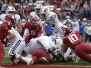 BYU running back Tyler Allgeier, top center, reaches for a touchdown during the second half of an NCAA college football game against Washington State, Saturday, Oct. 23, 2021, in Pullman, Wash. BYU won 21-19.