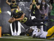 Oregon running back Travis Dye (26) dives into the end zone over California safety Daniel Scott (32) during the second quarter of an NCAA college football game Friday, Oct. 15, 2021, in Eugene, Ore.