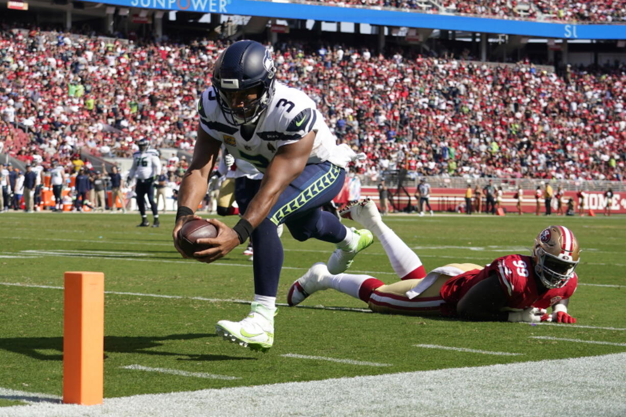 Seattle Seahawks quarterback Russell Wilson (3) runs for a touchdown past San Francisco 49ers defensive tackle Javon Kinlaw (99) during the second half of an NFL football game in Santa Clara, Calif., Sunday, Oct. 3, 2021.