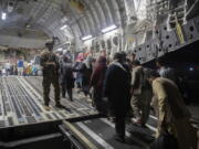 FILE - In this Aug. 22, 2021, file photo provided by the U.S. Air Force, Afghan passengers board a U.S. Air Force C-17 Globemaster III during the Afghanistan evacuation at Hamid Karzai International Airport in Kabul, Afghanistan. An Afghan man who worked for the U.S. government in Afghanistan says the Biden administration has ignored his pleas for help to evacuate his two young sons from Afghanistan after their mother died of a heart attack while being threatened by the Taliban. The International Refugee Assistance Project on Thursday, Oct. 7, 2021 filed a lawsuit against Secretary of State Antony Bilken on the man's behalf. The father fears for his children's safety and asked that he be identified only by his first name, Mohammad. (MSgt. Donald R. Allen/U.S.