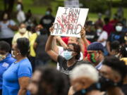 FILE - In this May 16, 2020, file photo, a woman holds a sign during a rally to protest the shooting of Ahmaud Arbery, in Brunswick, Ga. Arbery was shot and killed while running in a neighborhood outside the port city. Jury selection in the case is scheduled to begin Monday, Oct. 18. (AP Photo/Stephen B.